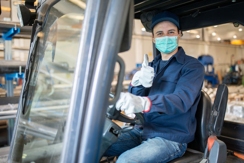 Warehouse workers use masks to follow safety protocols